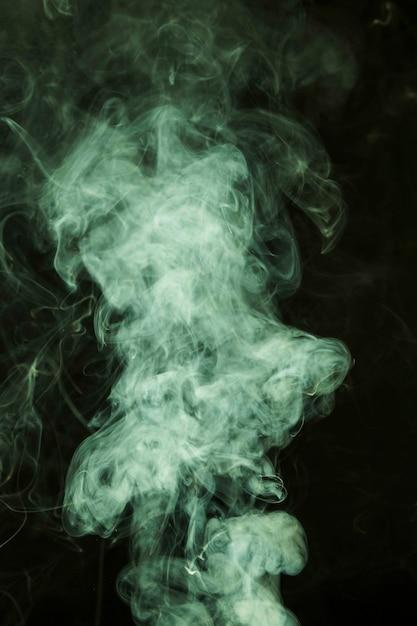 Fumée verte répandue sur fond noir Photo gratuit