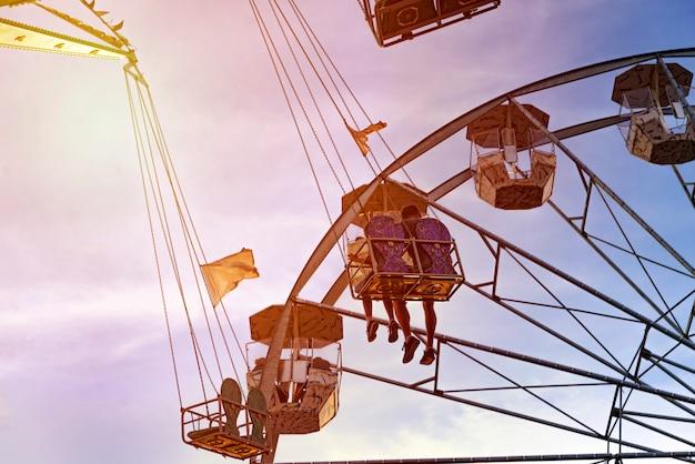 Fun dans le lunapark, les gens sur les montagnes russes et la grande roue, le coucher du soleil Photo Premium