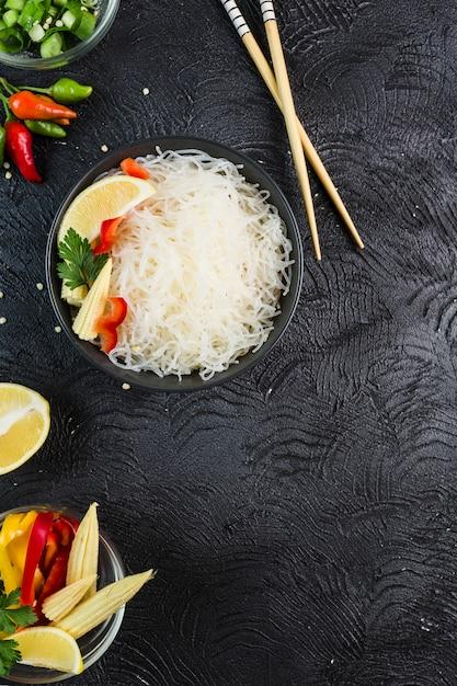 Funchosa De Nouilles De Riz Avec Des Légumes Dans Un Bol Noir Avec Des Baguettes Sur Un Fond Sombre, Vue De Dessus, Flatlay. Photo Premium
