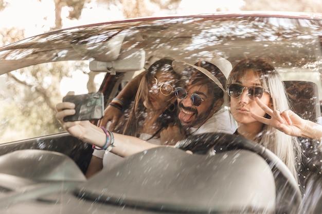 Funny friends prenant selfie à l'intérieur de la voiture sur téléphone mobile Photo gratuit