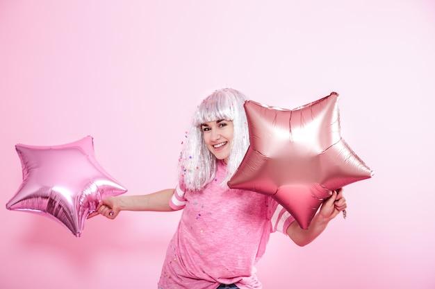 Funny Girl Aux Cheveux Argentés Donne Un Sourire Et Une émotion Sur Le Mur Rose. Jeune Femme Ou Adolescente Avec Des Ballons Et Des Confettis Photo Premium