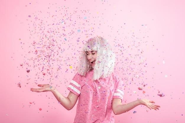 Funny Girl Aux Cheveux Argentés Donne Un Sourire Et Une émotion Sur Le Mur Rose. Jeune Femme Ou Adolescente Avec Des Confettis Photo Premium