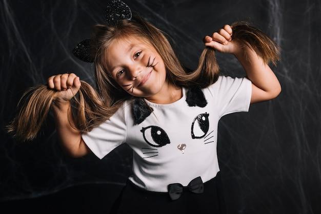 Funny girl en costume de chat touchant les cheveux Photo gratuit