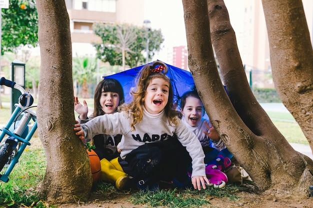 Funny girls assis sous l'arbre Photo gratuit