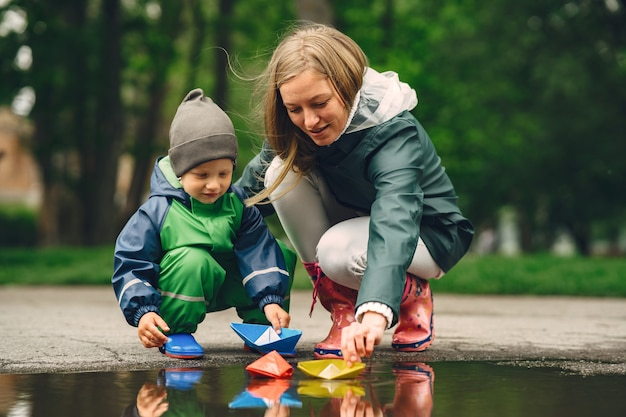 Funny Kid En Bottes De Pluie Jouant Dans Un Parc De Pluie Photo gratuit