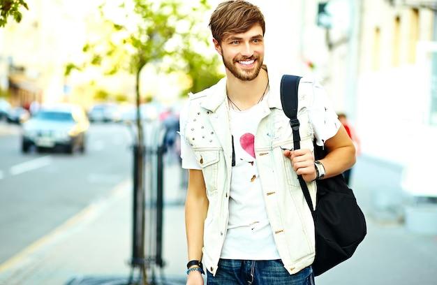 Funny Smiling Hipster Bel Homme Dans Des Vêtements D'été élégants Posant Sur Fond De Rue Photo gratuit