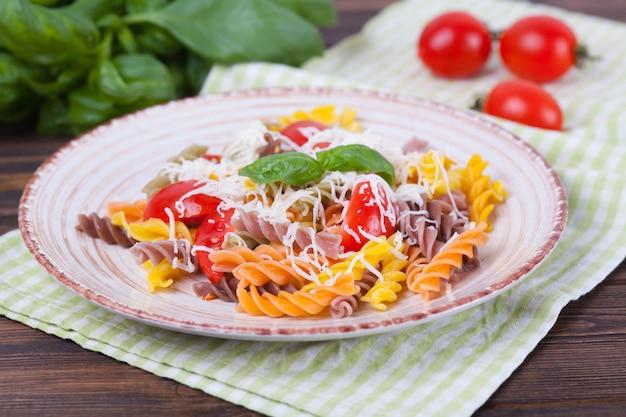 Fusilli colorés à la tomate, basilic et fromage sur une table en bois sombre Photo Premium