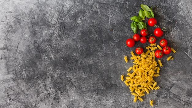 Fusilli crus avec des feuilles de tomates cerises et basilic sur fond de texture Photo gratuit