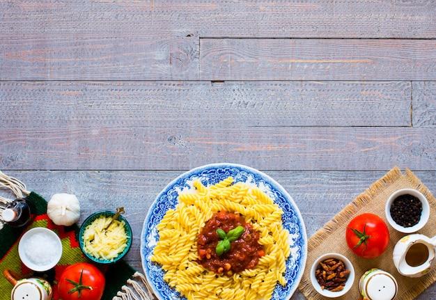 Fusilli à la sauce tomate et légumes sur une table en bois Photo Premium