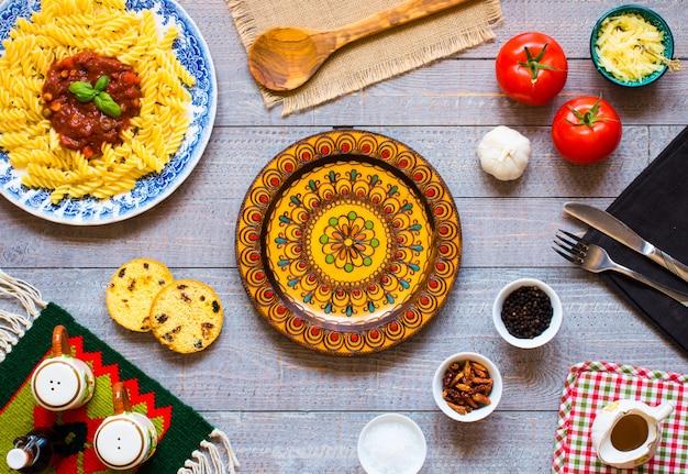 Fusilli avec sauce tomate, tomates, oignons, ail, paprika séché, olives, poivrons et huile d'olive sur bois Photo Premium