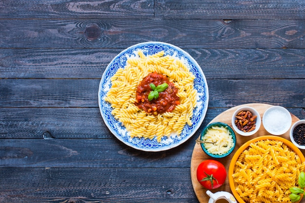 Fusilli à la sauce tomate, tomates, oignons, ail, paprika séché, olives, poivrons et huile d'olives. Photo Premium