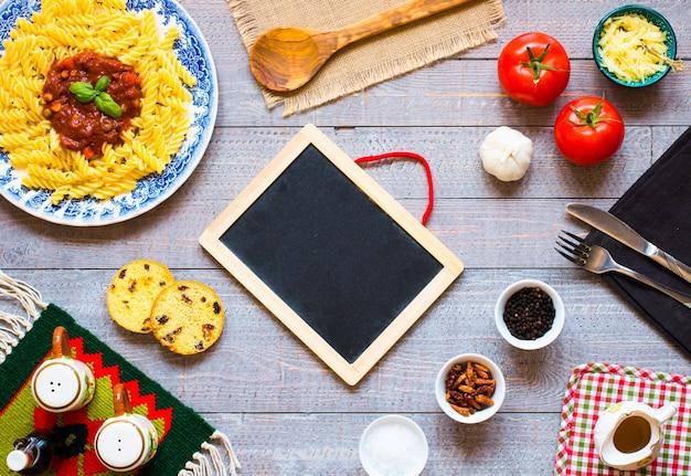 Fusilli à la sauce tomate tomates oignons ail séché olives de paprika poivron et huile d'olive sur un fond en bois. Photo Premium