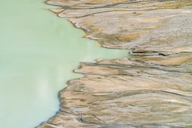 Fusion De Lac Et Tourbière Dans Les Montagnes. Les Ruisseaux Coulent Le Long Des Marais Dans Le Lac. De Nombreux Ruisseaux Coulent Des Montagnes. Eau Sombre De Vieille Couleur Turquoise. Paysage Texturé Inhabituel De La Nature De L'altaï. Photo Premium