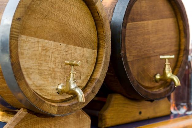 Fûts en bois pour le vin avec un robinet de métal jaune. Photo Premium