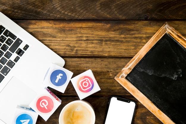 Gadgets électroniques, ardoise et café avec des icônes de médias mobiles et sociaux Photo gratuit