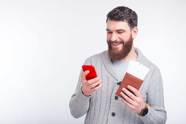 Gai Jeune Homme Fait L'enregistrement En Ligne Sur Son Téléphone Et Tient Son Passeport Avec Deux Billets Photo Premium