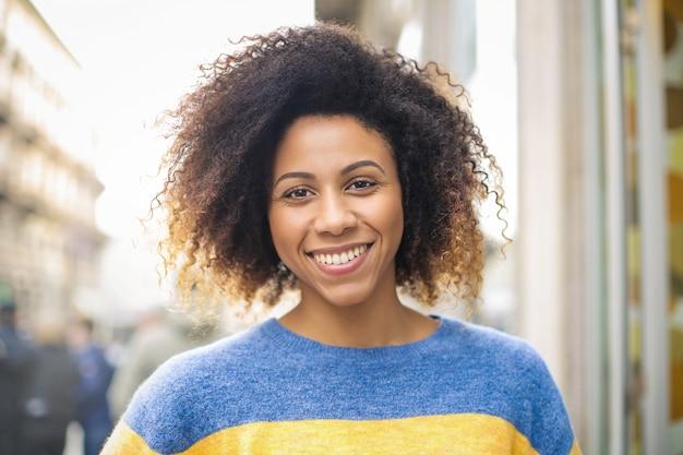 Gaie jeune femme souriante en se promenant dans la rue Photo Premium