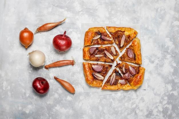 Galette de tarte à l'oignon à la française avec pâte feuilletée et divers oignons, échalotes, oignons rouges, blancs et jaunes, vue de dessus Photo gratuit