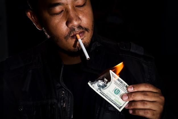 Un gangster utilisant un billet de banque pour allumer son tabac à cigarettes Photo Premium