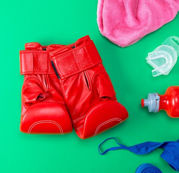 Gants de boxe en cuir rouge, une bouteille d'eau en plastique et une serviette rose Photo Premium