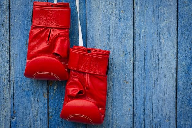 Gants de boxe en cuir rouge suspendus à une corde Photo Premium