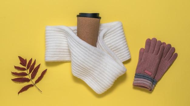 Des Gants Tricotés, Une écharpe, Un Verre De Café Et Une Feuille De Rowan Séchée Sur Fond Jaune. Ambiance D'automne. Photo Premium