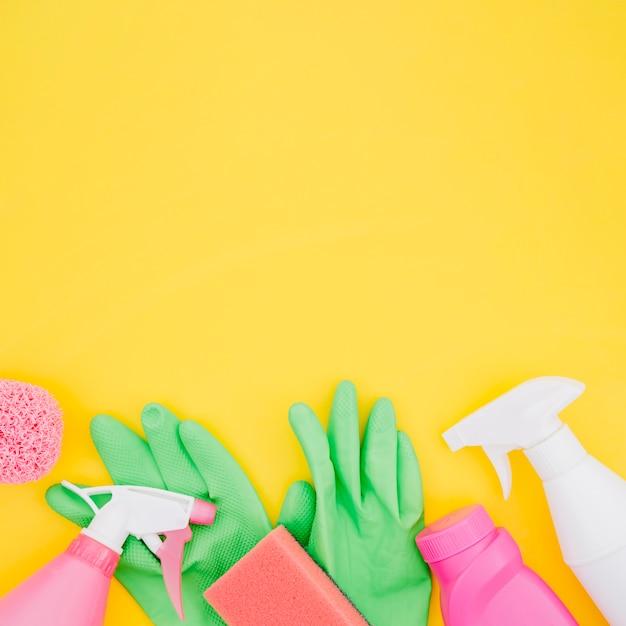 Gants verts; vaporisateur; bouteilles d'éponge et de détergent sur fond jaune Photo gratuit