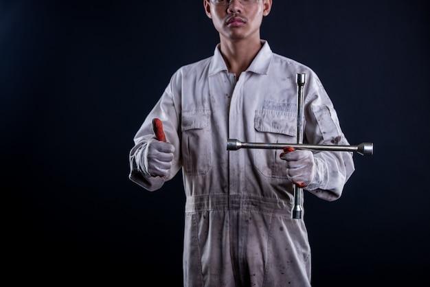 Garagiste portant un uniforme blanc tenant une clé Photo gratuit