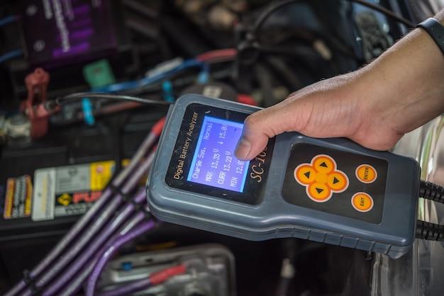Garagiste ou technicien vérifiant une batterie de voiture Photo Premium