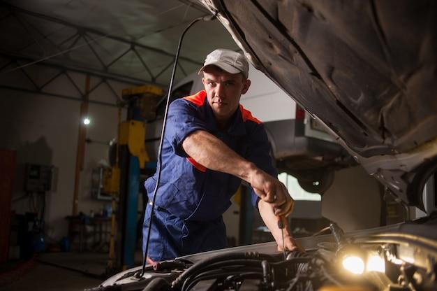 Garagiste travaillant dans le service de réparation automobile. réparation de voiture en utilisant Photo Premium