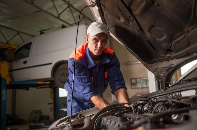 Garagiste travaillant dans le service de réparation automobile Photo Premium