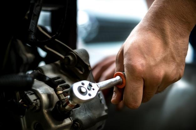 Garagiste utilisant une clé dynamo auto repair. Photo Premium