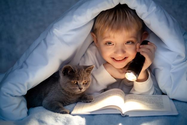 Un Garçon De 5 à 6 Ans Lit Un Livre Le Soir Dans L'obscurité Sous Une Couverture Avec Un Chaton Gris Britannique. Photo Premium