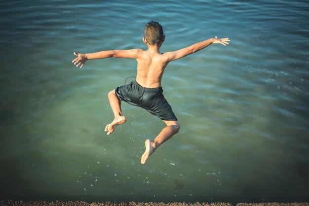 Garçon actif sautant dans l'eau Photo gratuit