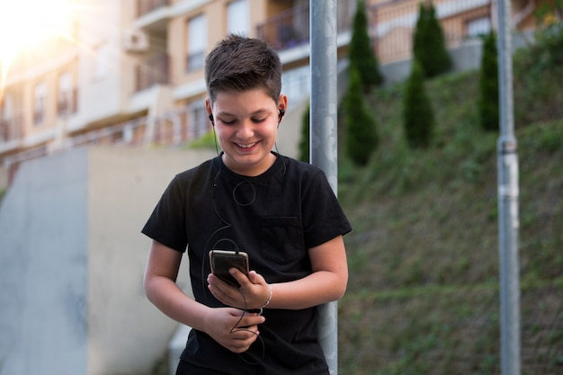 Garçon adolescent dans des vêtements décontractés, écouter de la musique sur son téléphone portable. Photo Premium