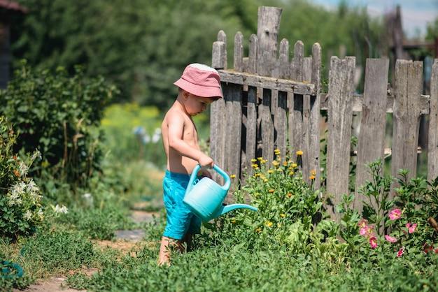 Un garçon arrose des fleurs dans le jardin. Photo Premium