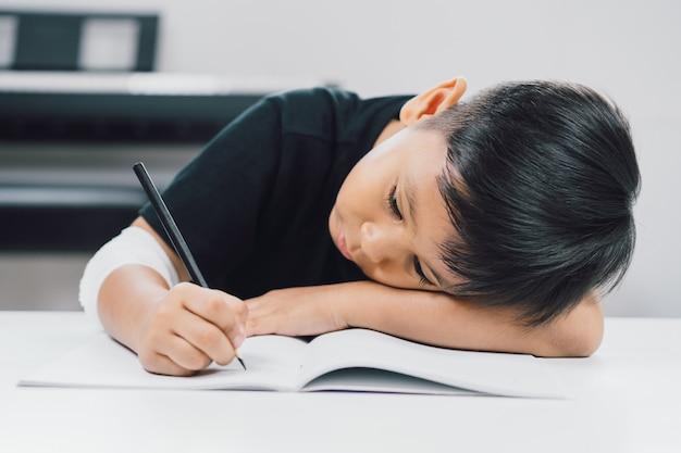 Un garçon asiatique aux mains blessées écrit un cahier. Photo Premium