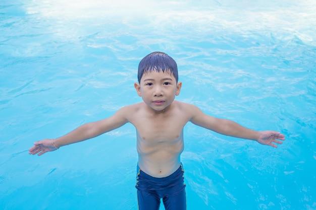 Garçon asiatique écarter les bras en jouant dans la piscine Photo Premium