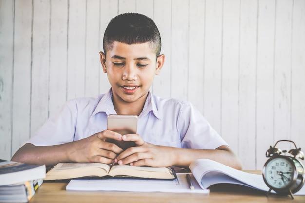 Garçon asiatique jouant au téléphone portable à l'école Photo Premium