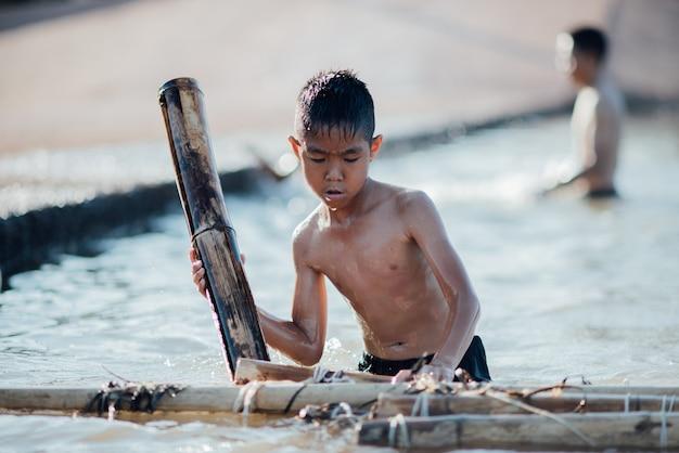 Garçon asiatique jouant un bateau en bois dans la rivière Photo gratuit