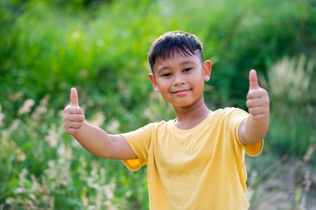 Garçon asiatique jouant dans la nature est un pouce levé Photo Premium