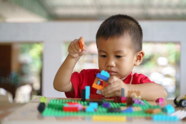 Garçon asiatique joue des blocs de construction Photo Premium