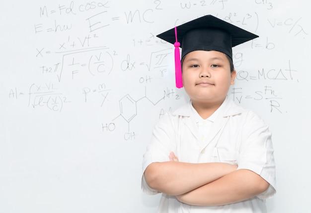 Garçon asiatique mignon scientifique porter chapeau de graduation sur whiteborad avec équation scientifique, science et edu Photo Premium