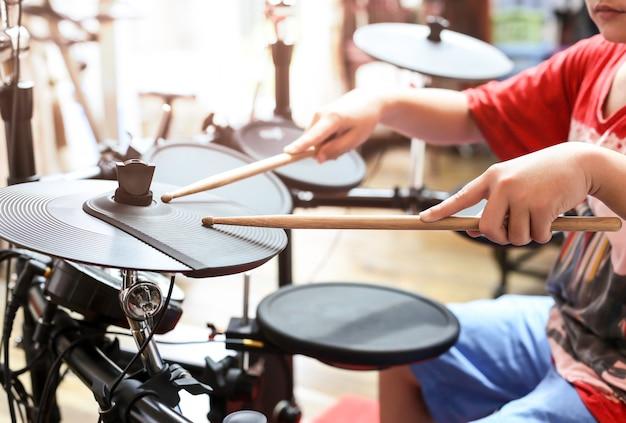 Un garçon asiatique non identifié joue un tambour électronique à tambour électronique Photo Premium