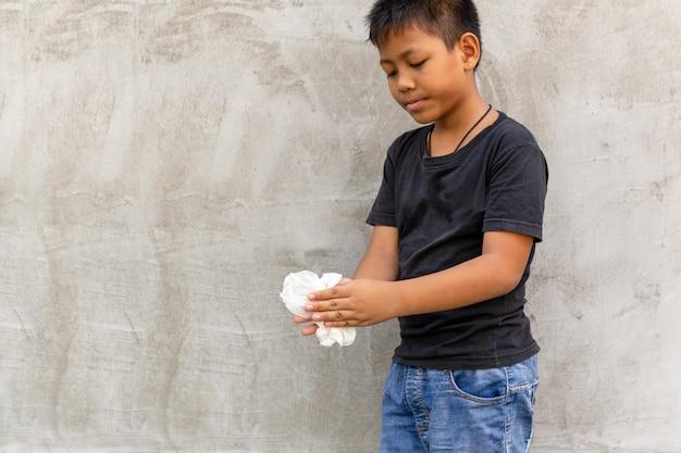 Garçon asiatique se nettoyant les mains avec un chiffon humide. Photo Premium
