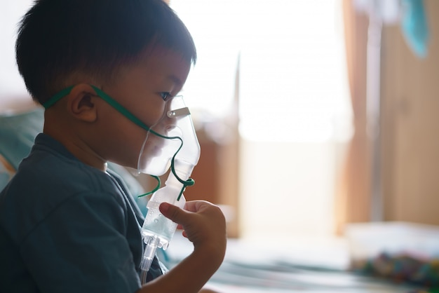 Garçon asiatique utilisant un inhalateur contenant un médicament pour arrêter la toux Photo Premium