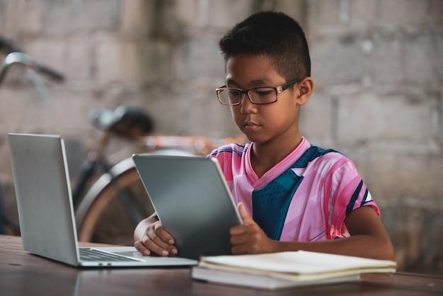 Garçon asiatique utilisant un ordinateur portable sur la table, revenez à l'école Photo gratuit