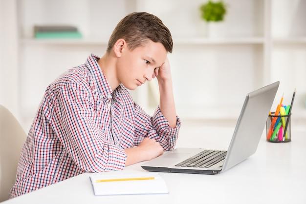Garçon assis au bureau avec ordinateur portable et faire ses devoirs. Photo Premium