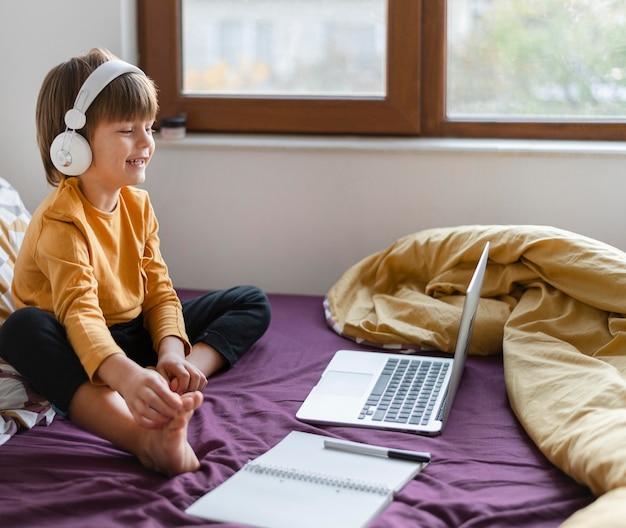 Garçon Assis Dans Son Lit Et Apprenant Tout En Portant Un Casque Photo gratuit