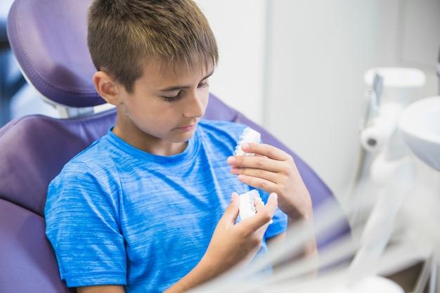 Garçon assis sur un fauteuil dentaire, regardant les dents en plâtre Photo gratuit
